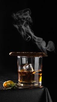 검은 배경에 유리 잔에 코냑, 럼, 위스키 또는 기타 알코올 음료