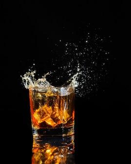Cognac splashing with ice isolated