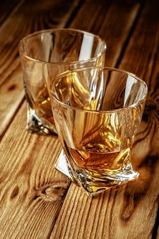 Cognac or whiskey in glasses on rustic table