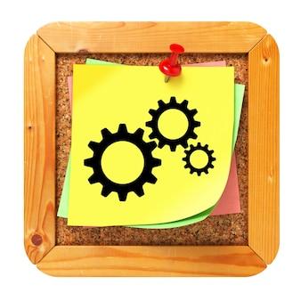코르크 메시지 보드에 노란색 스티커에 톱니 기어 아이콘.