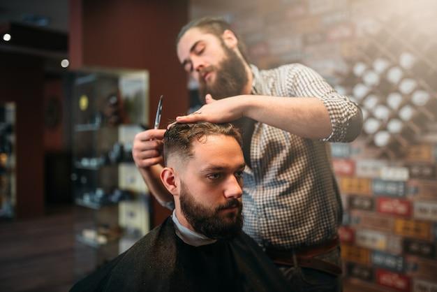 Парикмахерская, стрижка ножницами, волосы покупателя в черной салонной накидке