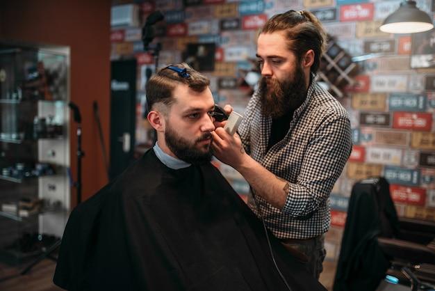 Парикмахер стрижет волосы мужчины-клиента в черном салоне-накидке.