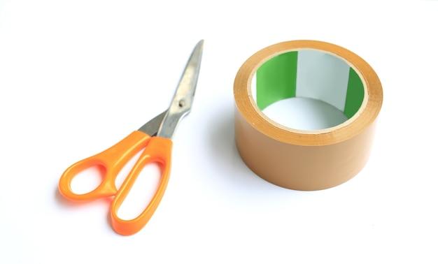 Катушка скотч и ножницы, изолированные на белом фоне. универсальное упаковочное оборудование. выборочный фокус
