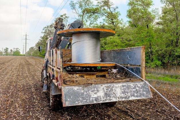 車輪付きトラックに取り付けられた高電圧ケーブル付きコイル。高電圧サポートへのケーブルの取り付け