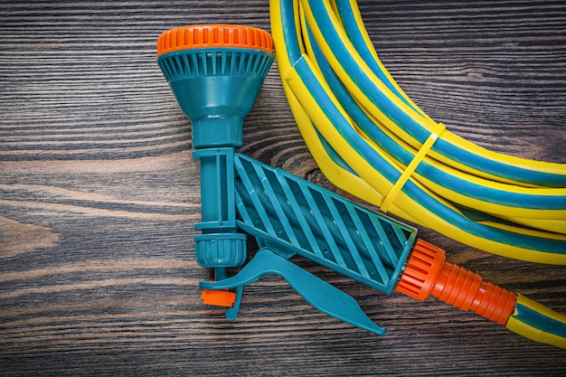 Coiled rubber hose on wooden board