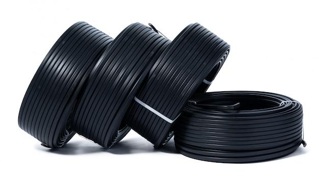 Катушки черного кабеля, изолированные на белом