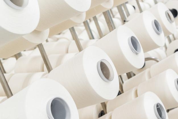 Катушки из белых хлопчатобумажных ниток на металлических стойках. закрыть