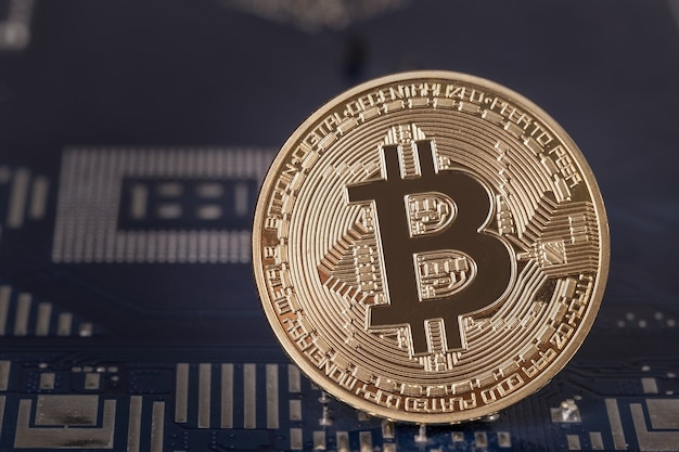 Coin bitcoin on the motherboard close-up. cripto