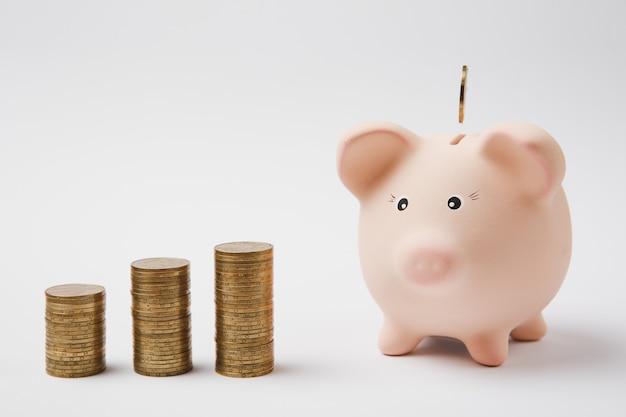 분홍색 돼지 저금통에 떨어지는 동전, 흰색 배경에 격리된 황금 동전 더미. 돈 축적 투자 은행 또는 비즈니스 서비스 부의 개념. 공간 광고를 조롱하십시오.