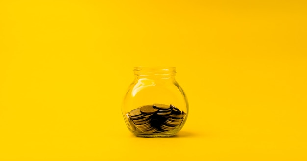 Coin in glass bottle to save money financial business investment ideas copy space for your text. on a yellow background