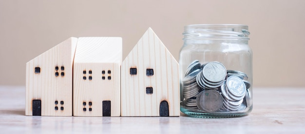 Coin in glass jar and wooden house model on table background.