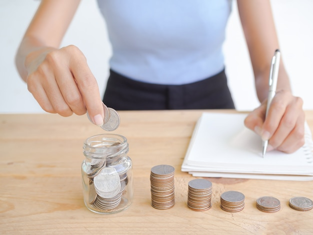 Coin in jar and stack cash on wood with blur image of slim and skin tan woman writing plan to saving money