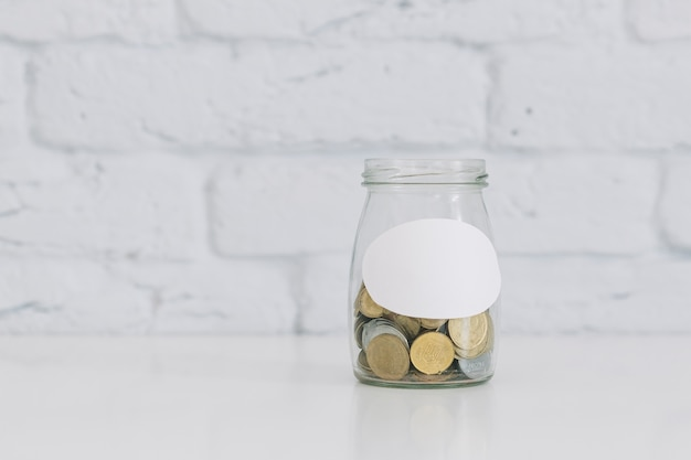 Coin jar on white desk against white wall