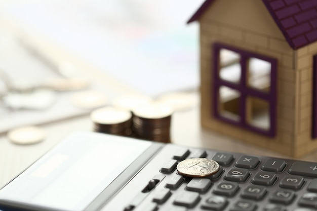 Coin lay on calculator, house model on office desk