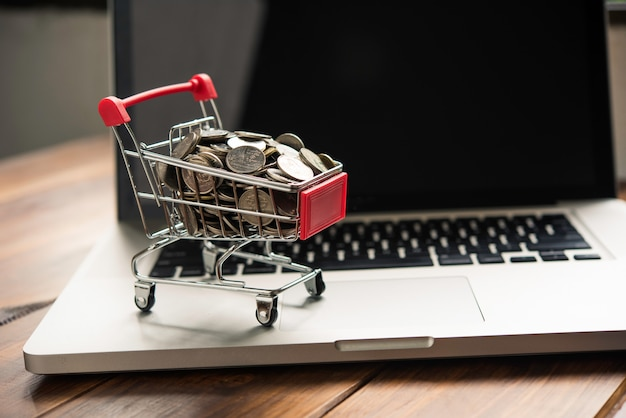 Coin in mini shopping cart on table for work and laptop for work to shopping online concept