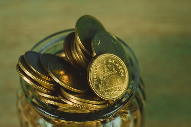 Coin money in the glass jar on table with green background