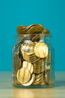 Coin money in the glass jar on table with green scene