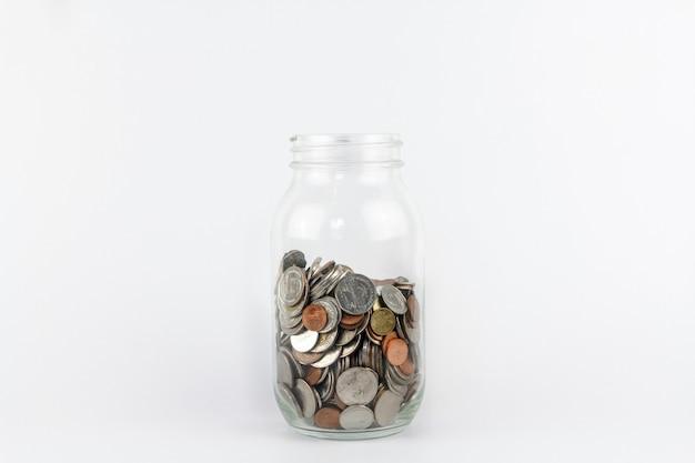 白い背景の上のコインmoneyinガラス瓶。貯蓄と金融セキュリティの概念。貯蓄銀行。