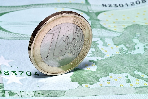Монета один евро на банкноте в сто евро
