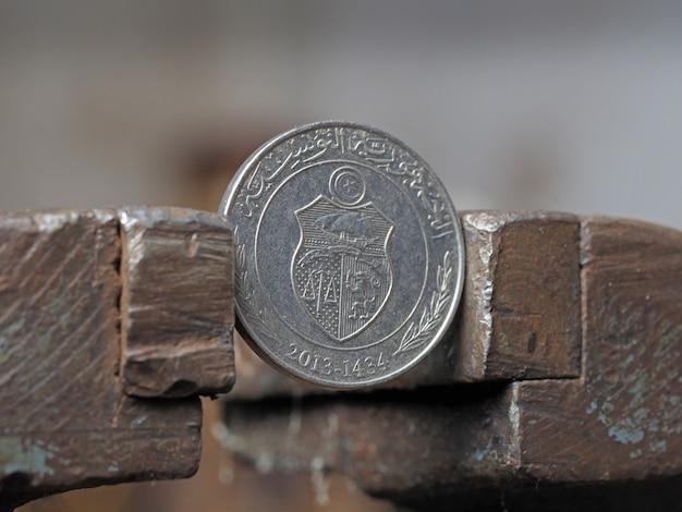 Монета один тунисский динар, зажатый в металлическом тиске