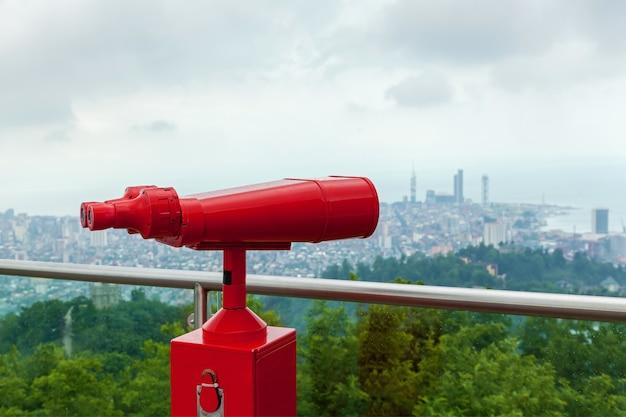 바다와 도시를 볼 수 있는 전망대에서 동전으로 작동되는 빨간색 쌍안 타워 뷰