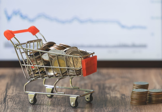 Coin in shopping cart with stock market board