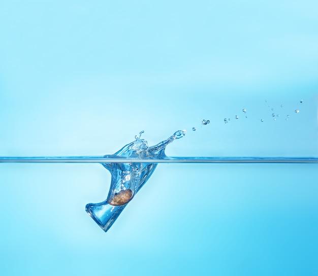 不安定な通貨の象徴として水に飛び散るコイン。お金、経済、危機、グローバリゼーションの概念。