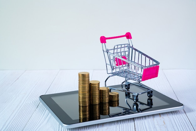 Coin stack and shopping cart trolley on tablet
