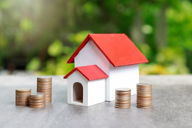 Coin stack with house model on green.