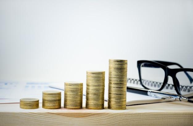 Монеты сложены, растут с очками и канцелярскими принадлежностями на деревянном столе