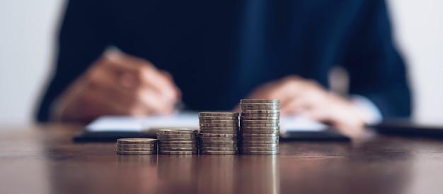 돈, 금융 비즈니스 성장을 쌓아 동전. 남자는 문서에 서명하고 있습니다.