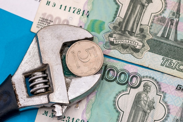 Coin in vise with ruble banknotes