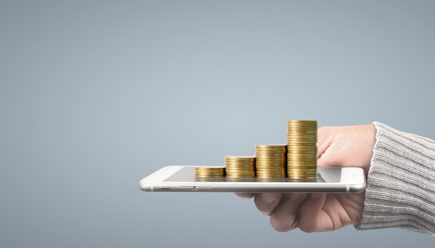 Coin and wealth concept. loads of money on glass representing digital tablet
