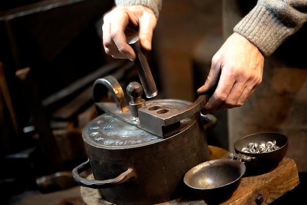 ハンマーとアンビルでコインを押すコイン職人。ビンテージスタイルの手工芸品のコンセプト