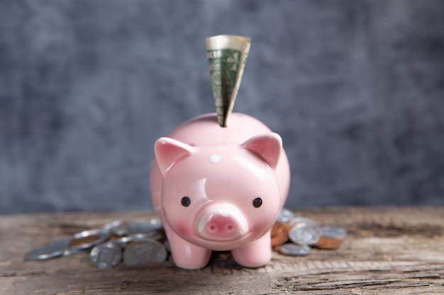 테이블에 달러 지폐가 있는 동전과 돼지 저금통