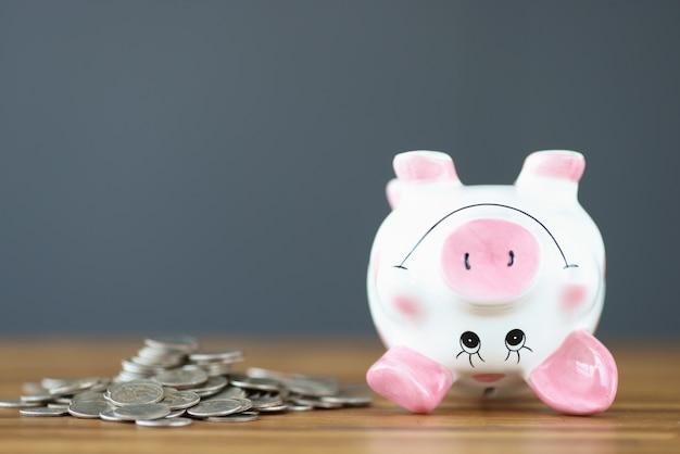 동전과 거꾸로 된 돼지 저금통이 테이블에 누워