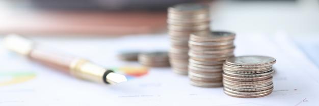 Монеты и шариковая ручка, лежащие на документе с графической экономией крупным планом в бизнес-концепции