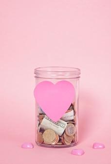 유리 돈 항아리, 재정 기부, 자선 개념의 동전과 지폐
