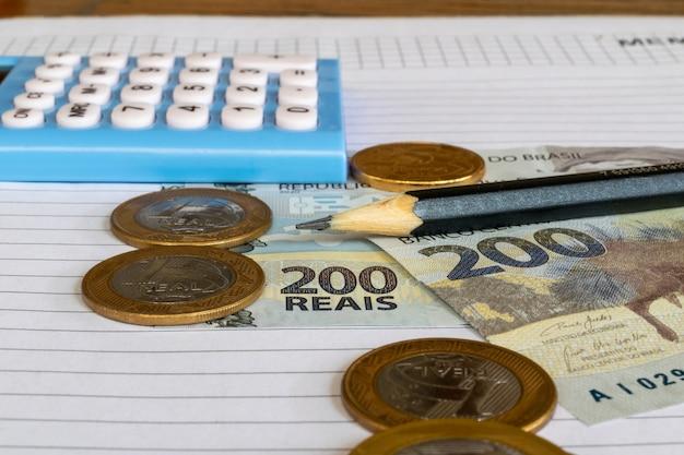 ブラジルのお金の計算機と鉛筆のコインと紙幣は、ブラジルのテーブルにあります