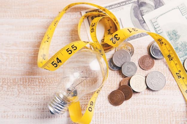 Монеты и сантиметр рядом с лампочкой