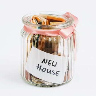 Coins and euro notes in the glass jar decorated with pink ribbon collected for new house