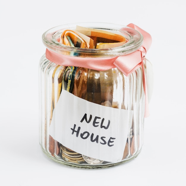 Монеты и ноты евро в стеклянной банке, украшенной розовой лентой, собранной для нового дома