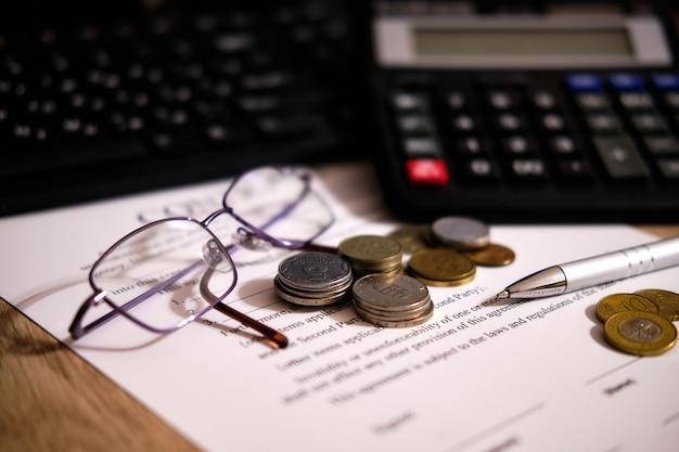 계산기와 펜 근처에서 계약을 체결하는 동전과 안경