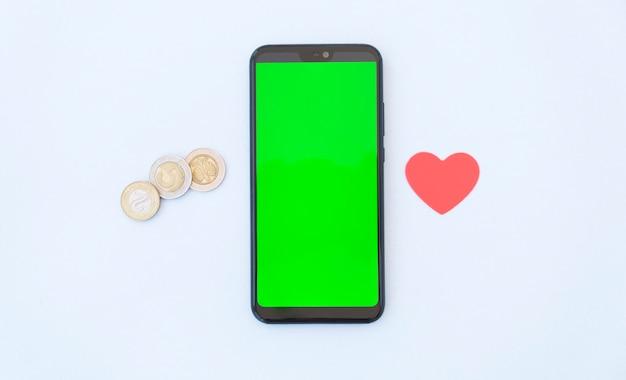 白で隔離画面上の空白のコピースペースとスマートフォンの近くのコインとハート