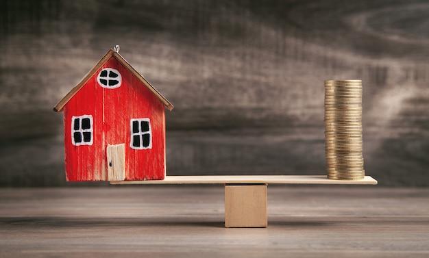 バランスのとれた木製のはかりのコインと家。