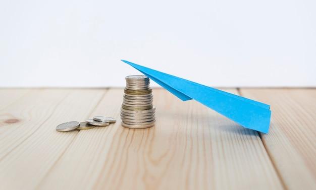 나무 테이블에 동전과 종이 항공기, 비즈니스 개념.