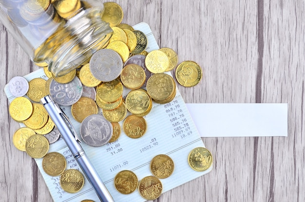 空白のラベルが付いている銀行口座帳のコインと銀のペン
