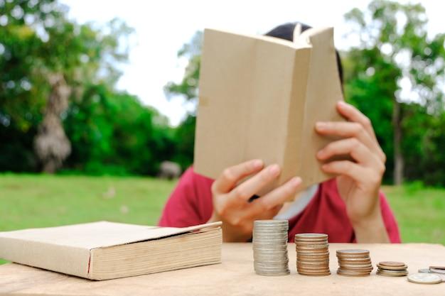 Монеты и стопки книг на деревянном столе. принимает деньги на образование и будущее.