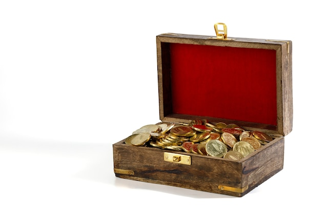 The coins are gilded in a wooden old chest with red velvet on the lid, isolated on white