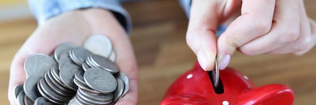 コインは赤い貯金箱の個人貯蓄と貯蓄の概念に投げ込まれます